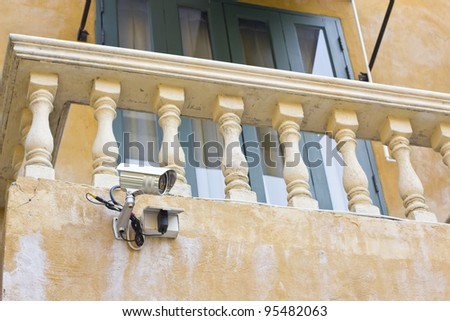 Security camera on vintage building, technology concept