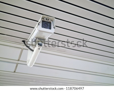 security camera on wall in public space indoor - stock photo