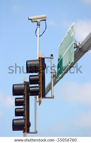Security camera with traffic light and sign.