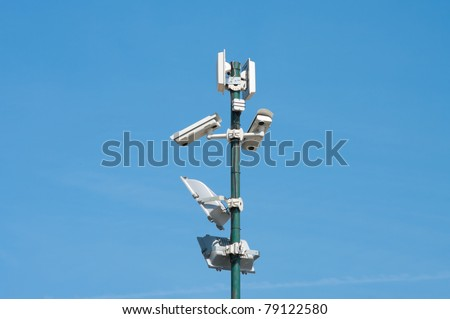 security cameras and floodlights mounted high on a pole to oversee an industrial area