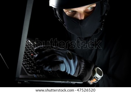 Security concept with dangerous man thief and laptop at night, internet crime online