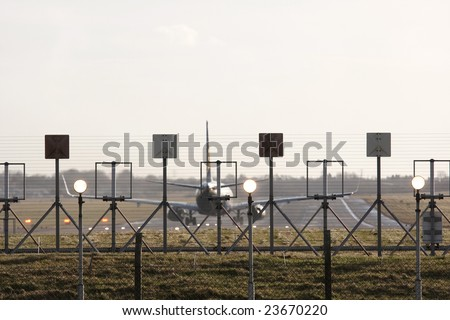 security fence around airport with jet ready to take off in background