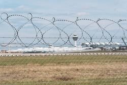 Security fence at the airport  In the background are blurred runway and other airport buildings like tower and terminal  Airport security concept