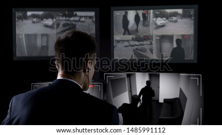Security guard in earphones watching robbery attempt on surveillance cameras ストックフォト ©