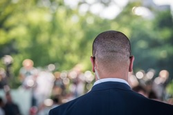 Security guard listening to his earpiece on event. Back of jacket showing. secret service guard. private bodyguard. man with earpiece in crowd. Black suit and bald head