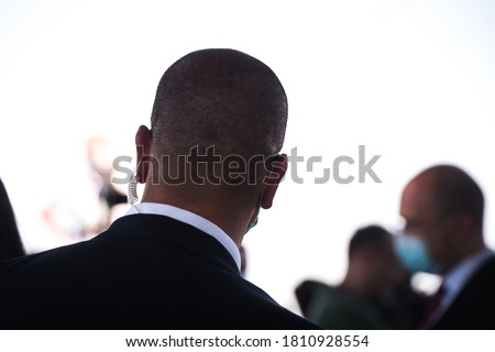 Security guard listening to his earpiece on event. Back of jacket showing. secret service guard. private bodyguard. man with earpiece in crowd. Black suit. Сток-фото ©