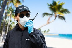 Security Guard Standing In Face Mask At The Beach