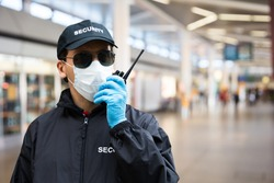 Security Guard Standing In Face Mask In Airport Terminal