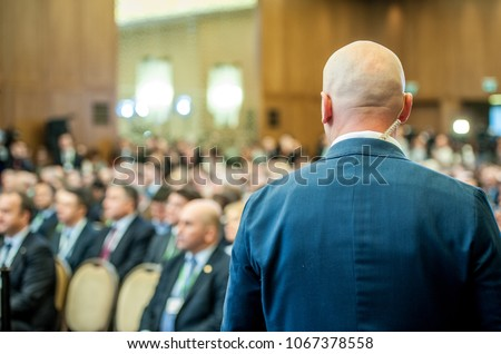 Security guard standing in the business meeting. Mature security guard listening to earpiece against Crowd. Secret service agent listening to his earpiece, side.