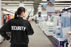Security guard using portable radio transmitter in shopping mall, space for text
