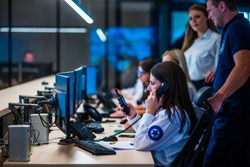 Security guards working in surveillance room. Female security guard with portable transmitter monitoring cameras indoors at night.