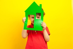 Security in the house. The child holds a large mock-up of the green house and hides in the house peeping through the windows. Stay home during coronavirus quarantine. Studio bright yellow background