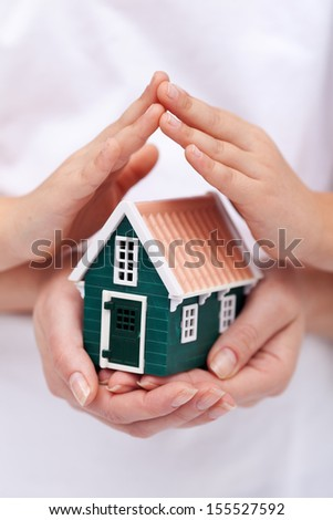 Security, insurance and safety concept with house protected by hands