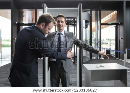Security man check businessman at entrance in office building or airport
