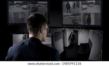 Security man monitoring corporate surveillance camera indoors, safety concept