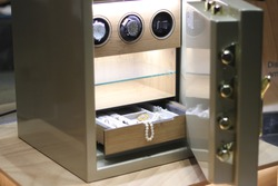 Security metal safe with pearl necklace, diamond jewelry and expensive watches inside