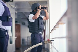 Security officer is performing a Pirate attack drill onboard of a cruise ship sailing the Red Sea off the Somalia coastline. The Captain is super-visioning the operational services with the crew