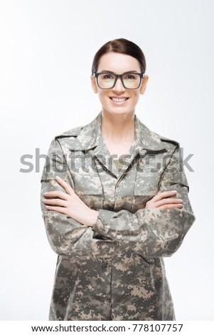 Security on board. Beautiful positive appealing woman staring at the camera   and wearing glasses and military uniform while crossing arms