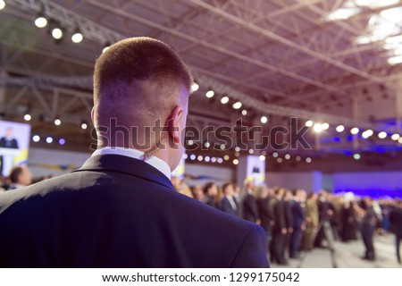 Security on public event. Secret guard service.  Private bodyguard with earpiece standing among crowd. Safety of govern and business meeting. Secret service agent listening to his earpiece, side. Сток-фото ©