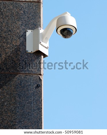 Security / surveillance camera against a clear blue sky