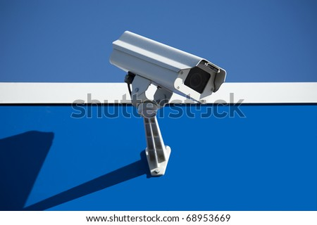 Security surveillance camera on the side of an industrial building