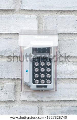 Security system keypad by entrance door. White brick wall. Portrait. #1527828740