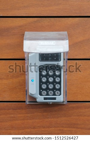 Security system keypad by entrance door. Wooden wall. Portrait. #1512526427