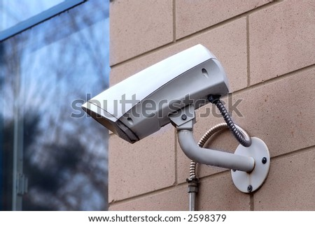 Security video camera on outside wall of a building