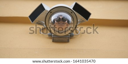 Security video camera on the yellow wall. Security video camera mounted on wall. Security video camera with four small cameras ストックフォト ©