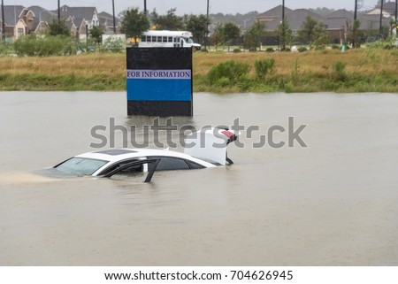 Sedan car swamped by flood water in Humble, Texas, US by Harvey Tropical Storm. Flooded car under deep on heavy high water road. Disaster Motor Vehicle Insurance Claim Themed. Severe weather concept #704626945