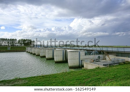 Sediment retention and tide flushing control dam with hydraulic valve gates engineering project over the Couesnon river at Bay of Mont Saint Michel in the Normandy region of France