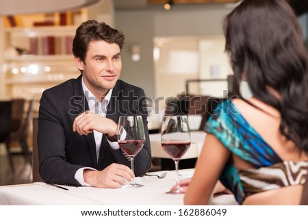 Seducing  handsome man looking at beautiful dark hair woman with wine glasses. Romantic and love mood