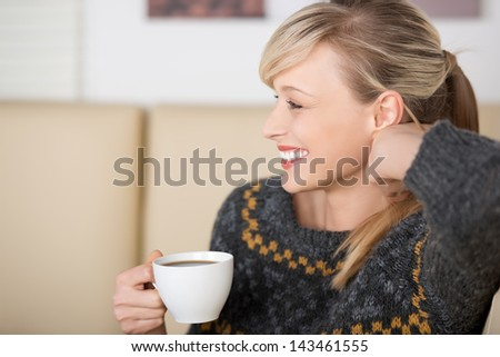Seductive blond woman smiling and playing with her hair while drinking a cup of coffee