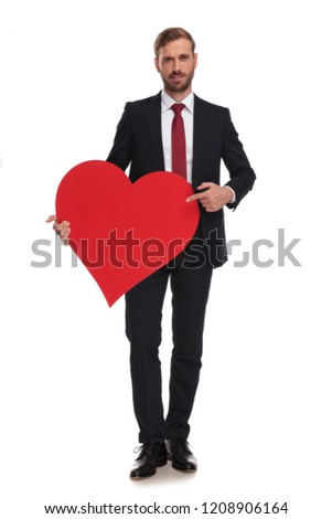 seductive businessman holds and shows big red heart while standing on white background, full body picture #1208906164