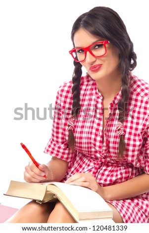 Seductive female student in a nerdy red dress and geek glasses studying, shot on white background