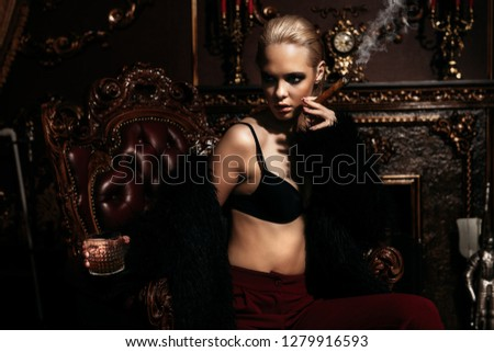 Seductive girl in the black bra, red pants and  fur jacket lying on a leather chair. Luxurious lifestyle. Fashion, beauty. Studio shot.