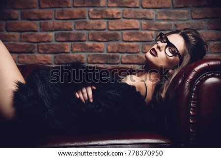 Seductive girl in the black lingerie and  fur jacket lying on a leather sofa. Luxurious lifestyle. Fashion, beauty. Studio shot.