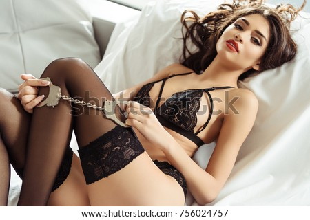seductive girl posing in black sexy lingerie with handcuffs on sofa