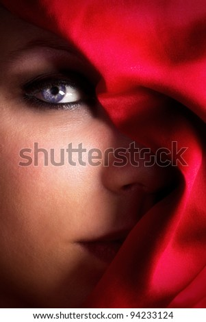 Seductive mystical dream girl with blue eyes and red scarf covering half of her face