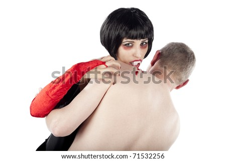 Seductive vampire woman biting a man and looking at the camera. Isolated on pure white background.