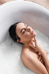 seductive woman with closed eyes relaxing in bathtub with milk