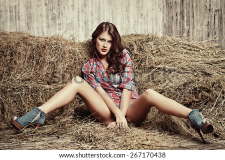 Seductive young woman in jeans shorts and a plaid shirt alluring on a hay. Denim fashion. Western style. Beauty, fashion.