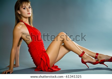 Seductive young woman wearing short red dress