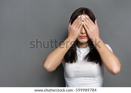 See no evil concept. Portrait of young scared woman covering eyes with hands while standing against gray studio background. Confused girl close eyes with palms ignoring something