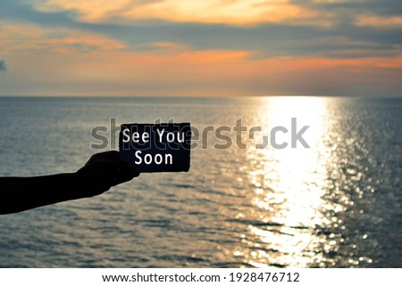See you soon text on hand holding torn paper with blurred background of sunset at the beach of Tanjung Aru Beach, Kota Kinabalu, Borneo,Sabah, Malaysia Сток-фото ©