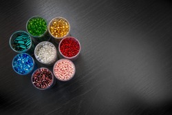Seed beads of different sizes in vials arranged as a flower in a top down perspective; A rainbow of colorful seed beads ready for beading