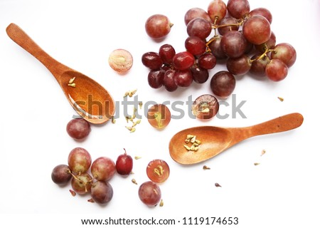 seeds and grape, grape-seed oil in wooden spoon on white background