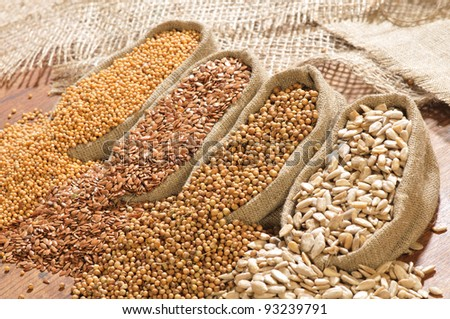 seeds of mustard, flax, coriander and sunflower are spilled from linen sacs