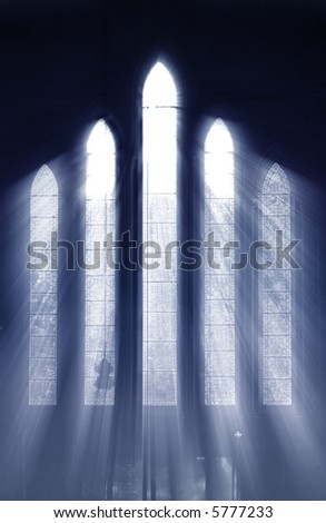 Seeing the light, shafts of light stream through stained glass window and onto cross below