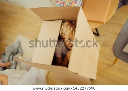 Seek and hide. Positive nice boy hiding in a box while playing seek and hide Stock photo ©